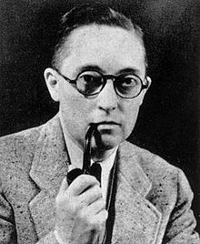 A black and white picture of Alan Hart smoking a pipe. He wears a light coloured suit and has on circular glasses.